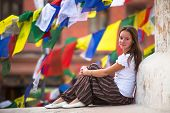 Young girl sitting on Buddhist stupa, prayer flags flying in the background.