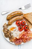 Healthy Full English Breakfast -  plate with poached eggs, sausages,  mushrooms, toasts and bacon, fruit, cup of fresh coffee and orange juice on white background