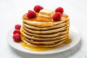 Big Pile of American  Pancakes with Raspberries, Melted Butter and Maple Syrup