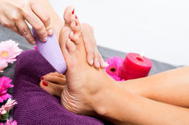 image of pumice-stone  - Woman having a pedicure treatment at a spa or beauty salon with the pedicurist massaging the soles of her feet with a pumice stone to cleanse dead skin and stimulate the tissue - JPG