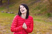 beautiful, happy girl with perky smile in red jacket is in the forest