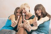 Portrait Of Three Young Ladies With Teeth Braces Together In Home Environment Showing Thumbs Up Cool