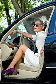 Girl driver. Woman driving a car in a sheath dress with a hat veil and sunglasses.