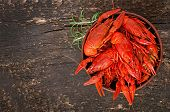 Bowl of fresh boiled crawfish on the old wooden background