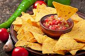 stock photo of nachos  - Mexican nacho chips and salsa dip in bowl on wooden background - JPG