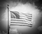 stock photo of flag pole  - Black and White of American flap flapping against a blue sky on a flag pole focus on star of waving flag