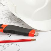 White Construction Helmet With Pencil And Box Cutter Knife Above Blueprint