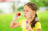 Cute little girl is blowing a soap bubbles
