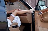 Wedding. Bride's leg in a garter and a shoe on a car's door. Young lady sitting out of the car.