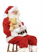 Santa Claus sitting in a chair holding teddy bears for Christmas