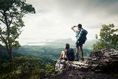 Hikers relaxing on top of the mountain and enjoying valley view