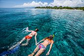 Two ladies snorkeling in tropical sea at sunny day