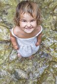 cute smiling toddler child girl on waterfall background