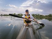 senior male is  paddling racing sea kayak  on a calm lake with storm clouds in background, Fort Coll