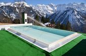 Swimming pool against snowy Alps. Switzerland