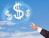 Hand pointing at dollar sign clouds on blue sky concept