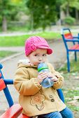 Toddler Girl Sitting And Drinks Water