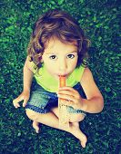 a young girl eating a frozen treat in the grass toned with a vintage retro instagram filter