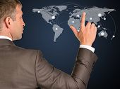 Businessman in a suit presses the virtual world map