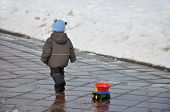 A Child Carries A Plastic String Trimmer