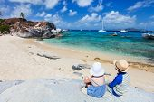 Back view of two kids sitting on granite boulder and enjoying beautiful scenery of The Baths beach a
