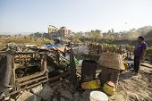 KATHMANDU, NEPAL - DEC 16, 2013: Unidentified poor people near their houses at slums in Tripureshwor