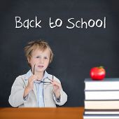 Cute pupil holding glasses against back to school message