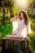 Young beautiful red hair woman wearing a transparent white blouse posing on a stump in forest