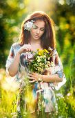 Young beautiful red hair woman holding a wild flowers bouquet in a sunny day. Attractive woman