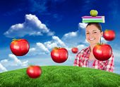 Pretty student holding an apple and books on her head against green field under blue sky