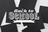 Back to school message against black paper strewn over notepad