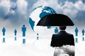 Mature businessman holding an umbrella against human figures surrounding earth graphic