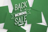 Back to school sale message against green paper strewn over notepad