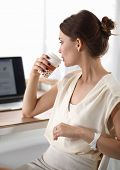 Attractive woman sitting at desk in office, working with laptop computer, having takeaway coffee