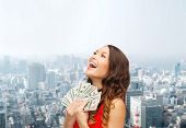 sale, city, estate, banking and people concept - smiling woman in red dress with us dollar money over cityscape background