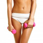 Perfect tanned woman with dumbbells isolated on white background.