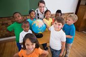 Cute pupils pointing to globe in classroom at the elementary school