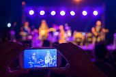 A Fan Watches A Gig Through His Mobile Phone.