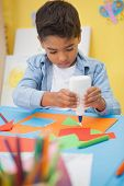 Cute little boy making art in classroom at the nursery school