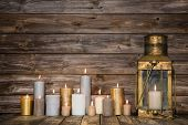 Wooden Background In With Many Burning Candles And A Old Rustic Lantern.