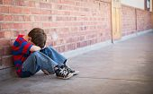 stock photo of pupils  - Sad pupil sitting alone in corridor at the elementary school - JPG