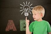 Cute boy pointing against abc drawn and coloured in on blackboard