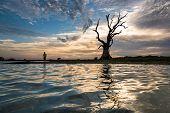 MANDALAY, MYANMAR - CIRCAR DECEMBER 2014 : A man appreciates beautiful sunset beside the signature d