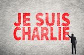 Asian businessman write text on wall, I am Charlie (In French)