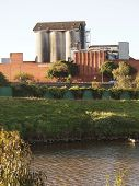 stock photo of silos  - Concrete Silo and factory by the river - JPG