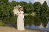 stock photo of century plant  - Young woman in white historical dress of XIX century with white umbrella in white hat near lake - JPG