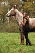 picture of appaloosa  - Beautiful girl with nice dress standing next to nice horse in autumn - JPG