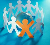 Paper people standing in a circle around glass globe isolated on blue background