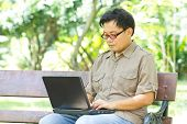 picture of work bench  - Asian man working with laptop in the park - JPG