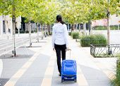 foto of carry-on luggage  - Closeup abstract backside view portrait of woman in light blue shirt carrying luggage walking through gray sidewalk of green trees background - JPG